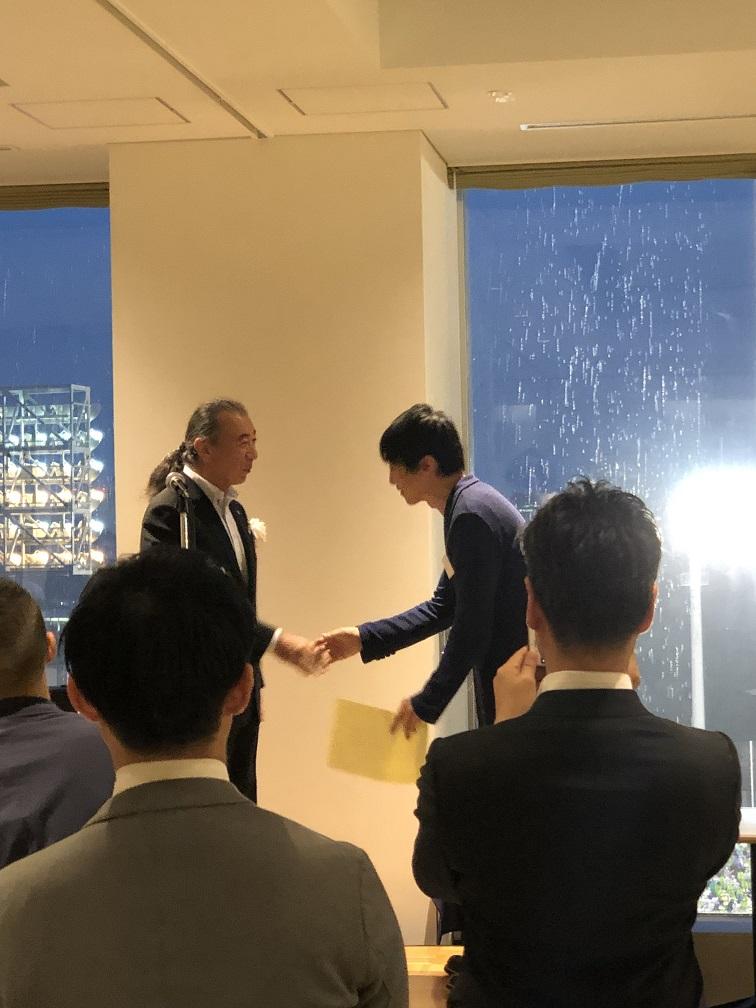 シダックス 志太会長より株式会社エボレボ代表取締役CEO小山が敢闘賞の賞状および賞品のワインをいただきました